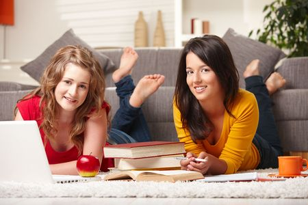 Happy teen girls lying on floor with laptop and books smiling at camera at home. photo
