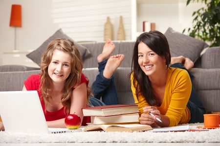 Happy teen girls lying on floor studying with laptop and books smiling at camera at home. photo