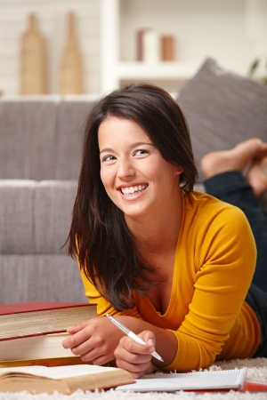 teenagers only: Happy teen girl learning on floor at home with books and pen in hand, smiling. Stock Photo