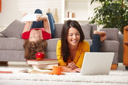 Happy teen girls studying at home in living room with books and laptop. photo