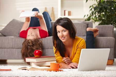prone: Teenage girls learning together at home with books and laptop, girl in front smiling at camera.
