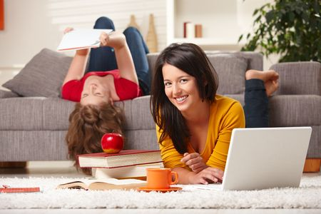 Happy students studying at home in living room with books and laptop, looking at camera smiling. photo