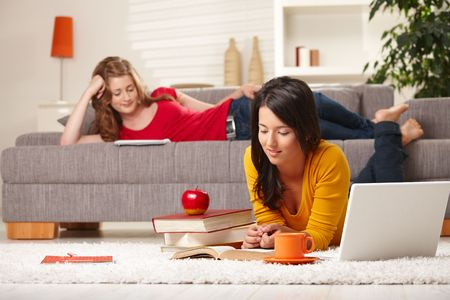 Teenage girls studying at home in living room lying on sofa and floor with books and laptop. photo