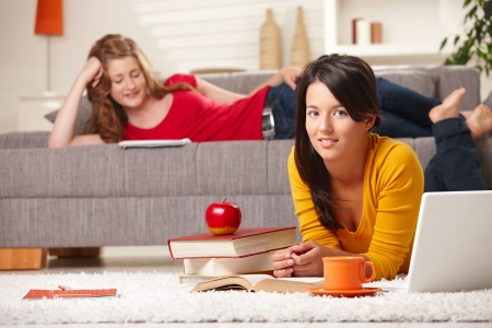 Teenage girls learning at home in living room with books and laptop, girl in front smiling at camera. photo