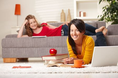 prone: Happy schoolgirls learning at home in living room with books and laptop, looking at camera smiling.