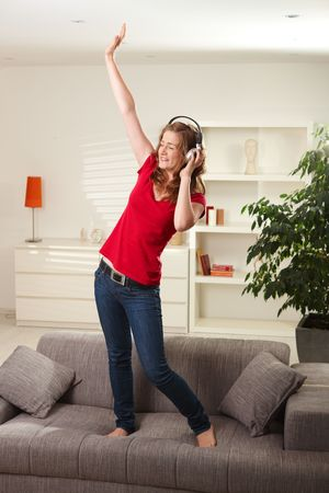 home entertainment: Happy teen girl listening to music on headphones dancing on couch at home with eyes closed smiling.
