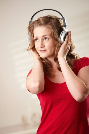 Portrait of happy teen girl listening to music holding onto headphones looking up. Stock Photo - 6373863
