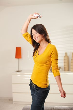 Happy teen girl dancing at home with earphones holding mp3 player smiling. Stock Photo - 6373869
