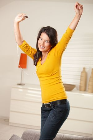 Happy teen girl dancing at home with earphones holding mp3 player smiling at camera. Stock Photo - 6373860