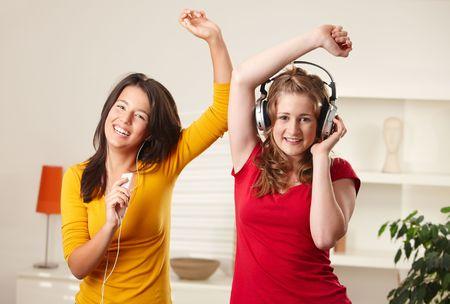 listening to music: Ni�as adolescentes escuchar m�sica divertirse juntos en casa bailando sonriente, contacto con los ojos.