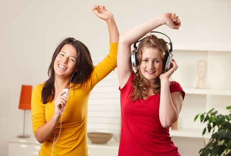 listening to people: Teen girls listening to music having fun together at home dancing smiling, eye contact.