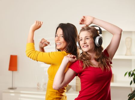 Happy teen girls listening to music having fun together at home dancing smiling. photo