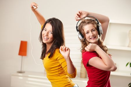 Happy teen girls listening to music via headphone and earphone having fun together at home dancing smiling at camera. photo