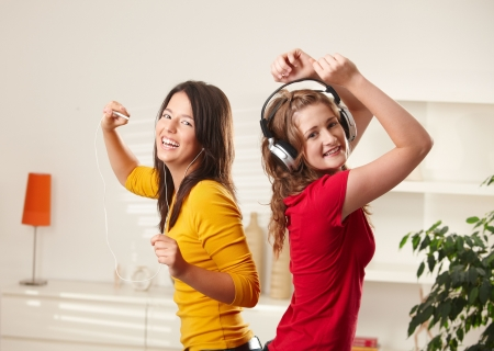 dancing pose: Happy teen girls listening to music via headphone and earphone having fun together at home dancing smiling at camera. Stock Photo