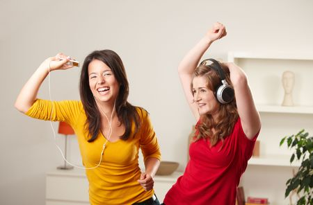 Happy teenage girls listening to music having fun together at home dancing smiling. photo