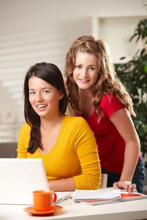 Two teenage girls smiling at camera with laptop on table at home. photo