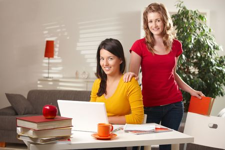 Highschool students learning at home with laptop computer and books looking at camera smiling. photo