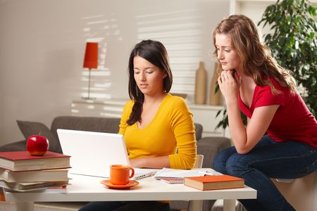 online learning: Two teenage girls watching laptop sitting at table at home.