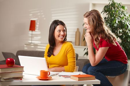 Happy teenage girls laughing together, sitting at table with laptop and books at home. photo