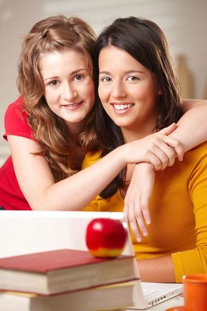 Two teenager girls hugging, smiling looking at camera. photo