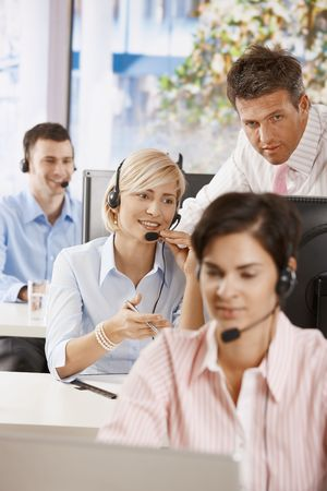 Manager controlling customer service operators in office. photo