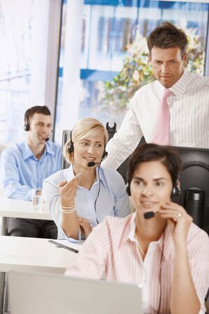 Manager checking customer service operators in office. photo