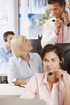 leading light: Manager checking customer service operators in office. Stock Photo