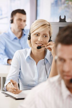 Young female customer service operator talking on headset, smiling. Stock Photo - 6374115