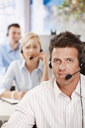 Portrait of customer service operator talking on headset, smiling. photo