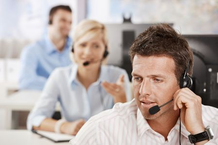 call center office: Portrait of customer service operator talking on headset, smiling. Stock Photo