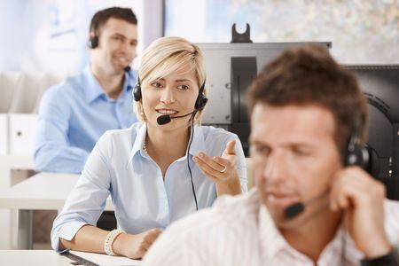 servicio al cliente: Los operadores de servicios de cliente j�venes que trabajan en la Oficina, sonriendo. Foto de archivo