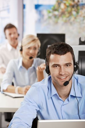 Young customer service operators working in office, smiling. Stock Photo - 6374281