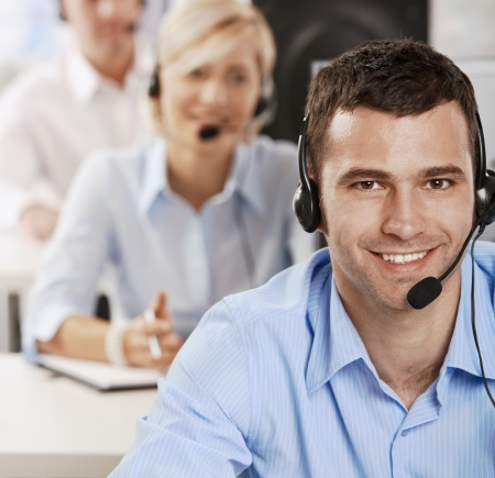 customer service representative: Young customer service operator talking on headset, smiling.