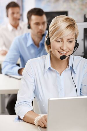 servicio al cliente: Retrato de operador del servicio de cliente joven hablando sobre el kit manos libres port�til, sonriendo.