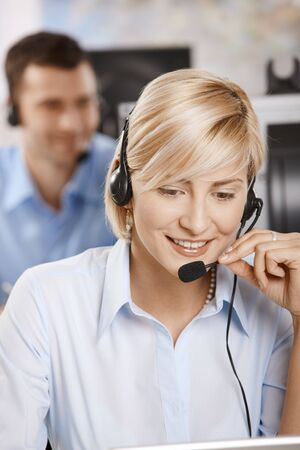 Portrait of young customer service operator talking on headset, smiling. photo
