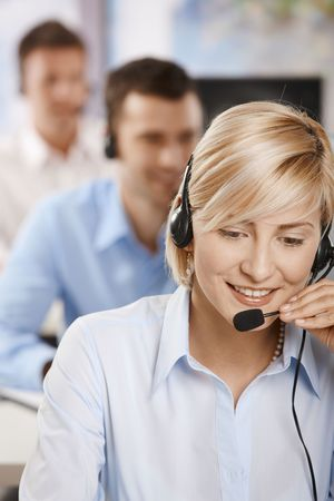 customer service representative: Portrait of young customer service operator talking on headset, smiling. Stock Photo
