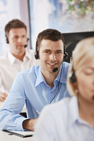 Young customer service operators working in office, smiling. photo