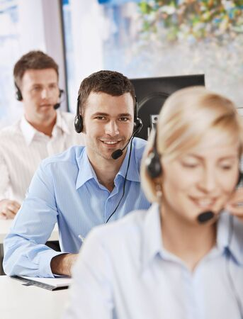 Young customer service operator talking on headset, smiling. photo