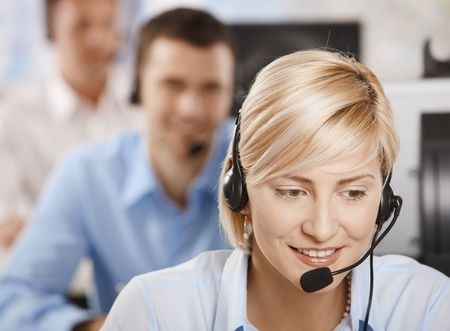 Portrait of young customer service operator talking on headset, smiling. Stock Photo - 6374200
