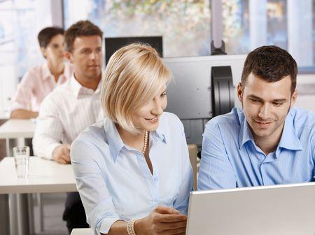 Jóvenes empresarios sentado en el escritorio, utilizando equipo en negocios, capacitación, sonriendo. Foto de archivo