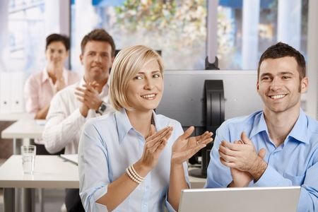 Happy business people sitting at desk in classrom, and clapping at the end of business training. photo