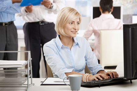 Happy young businesswoman using computer in bright office, colleagues working in the background. Stock Photo - 6374107