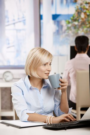 Young businesswoman sitting at office desk, drinking coffee. Stock Photo - 6374169
