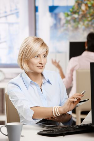 Young businesswoman working in office, checking data on screen holding notepad. Stock Photo - 6374151