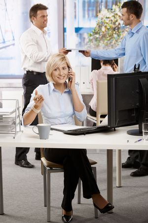 Young businesswoman sitting at office desk, talking on mobile phone. photo
