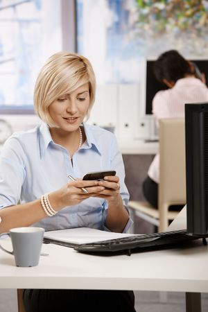 Young businesswoman sitting at office desk, using smart mobile phone. Stock Photo - 6374388