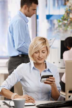 Young businesswoman sitting at office desk, using smart mobile phone. Stock Photo - 6374154