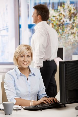 Happy young businesswoman using computer in bright office, colleagues working in the background. photo
