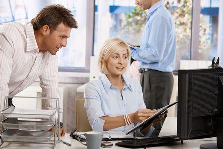 obreros trabajando: Empresarios trabajando juntos en la Oficina, mirando el Bloc de notas, sonriendo.