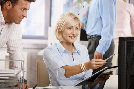 co work: Businesspeople working together in office, looking at notepad, smiling.